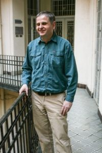 Rozemberczki Zoltán – Mosolygós, zöld inges férfi, körfolyosón állva.