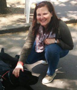 Eigner Anikó – Mosolygós nő, guggolva, kutyát simogatva.