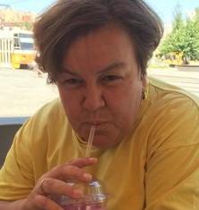Katona Andrea – Üdítőt szívószállal ivó nő, sárga felsőben.