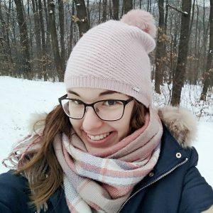Kertész Vivien – Mosolygós, sapkás, sálas, szemüveges nő, téli háttér előtt.