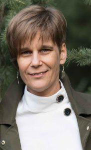 Kocsmárszky Judit – Mosolygós nő, rövid hajú, fenyőfa háttér előtt.