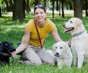 Mikola Gyöngyvér – Mosolygós nő a fűben ülve, három kutyával.Mikola Gyöngyvér – Mosolygós nő a fűben ülve, három kutyával.