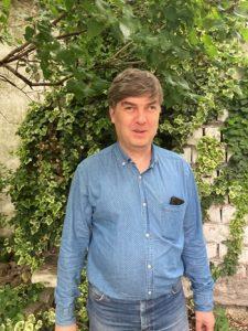 Molnár Ákos – Mosolygós, kék inges férfi, borostyános fal előtt állva.